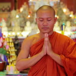 stock-footage-closeup-of-a-buddhist-monk-with-orange-robe-pray-in-temple